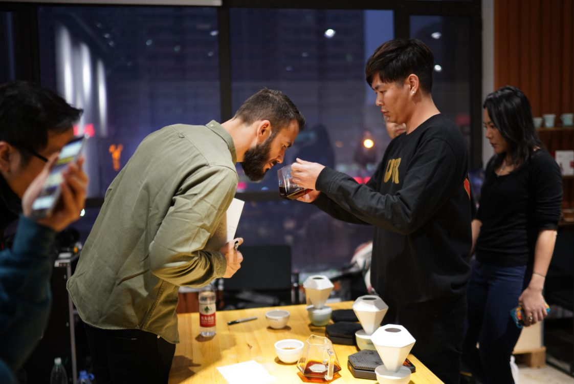 Stefanos Domatiotis is coaching a barista how to brew coffee