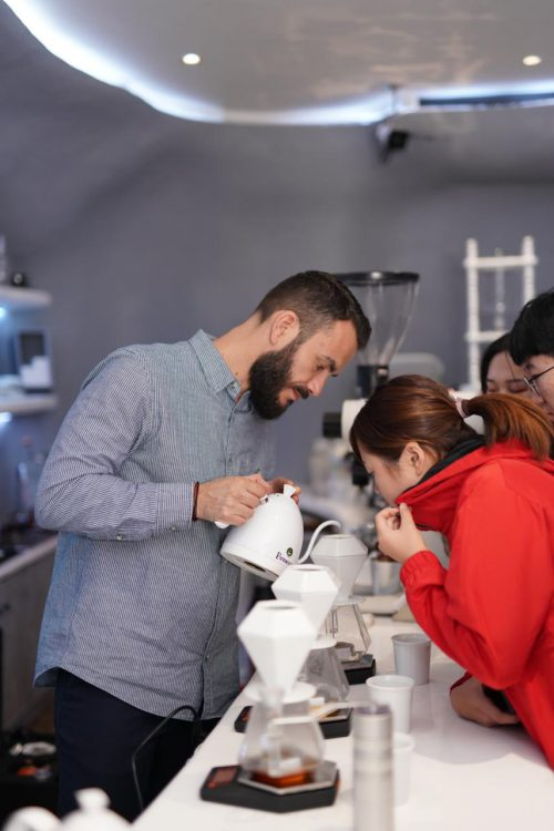 Stefanos Domatiotis is coaching a candidate how to use the brew devices
